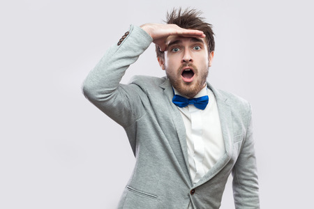 c917438a0ae4 Portrait of amazed handsome bearded man in casual grey suit and blue bow tie  standing looking