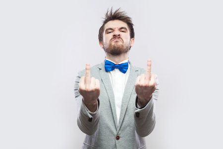 Portrait of angry handsome bearded man in casual grey suit and blue bow tie standing with middle finger fuck sing and looking at camera. indoor studio shot, isolated on light grey background. Imagens