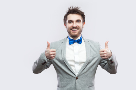 Portrait of satisfied handsome bearded man in casual grey suit and blue bow tie standing, thumbs up and looking at camera with toothy smile. indoor studio shot, isolated on light grey background.