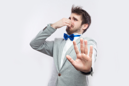 Dont get close. Portrait of handsome bearded man in casual grey suit and blue bow tie standing with blocking ban hand and pinching his nose. indoor studio shot, isolated on light grey background.