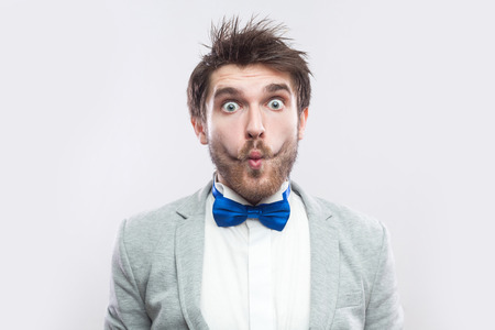 Closeup portrait of funny surprised handsome bearded man in casual grey suit, blue bow tie standing and looking at camera with big eyes and fish lips. studio shot, isolated on light grey background. Фото со стока