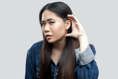 Portrait of attentive beautiful brunette asian young woman in casual blue jacket with makeup standing holding hand near ear and trying to spy or listen. studio shot, isolated on light grey background. 版權商用圖片