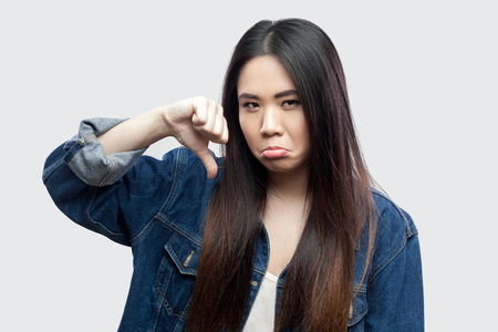 Portrait of dissatisfied beautiful brunette asian young woman in blue jacket with makeup standing and looking at camera with thumbs down and dislike. studio shot, isolated on light grey background. Stock Photo