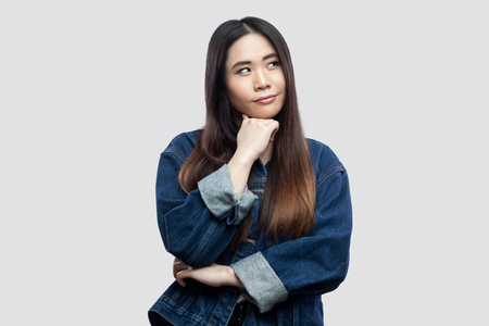 Portrait of thoughtful beautiful brunette asian young woman in casual blue denim jacket with makeup standing, confused looking away and thinking. indoor studio shot, isolated on light grey background. 写真素材