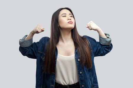 I am strong and independent. Portrait of proud satisfied beautiful brunette asian young woman in casual blue jacket and makeup standing with raised arms. studio shot, isolated on light grey background