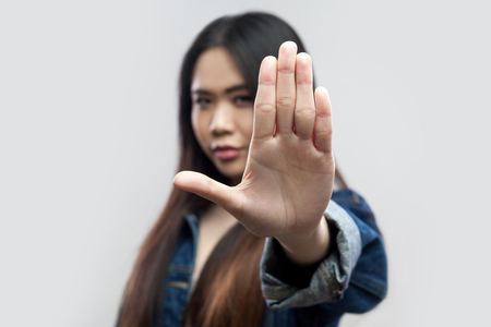 Stop! Portrait of serious beautiful brunette asian young woman in casual blue denim jacket, makeup standing with stop hand sign and looking at camera. studio shot, isolated on light grey background.