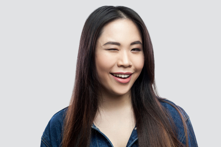 Portrait of funny beautiful brunette asian young woman in casual blue denim jacket with makeup standing with toothy smile winking and looking at camera. studio shot, isolated on light grey background.