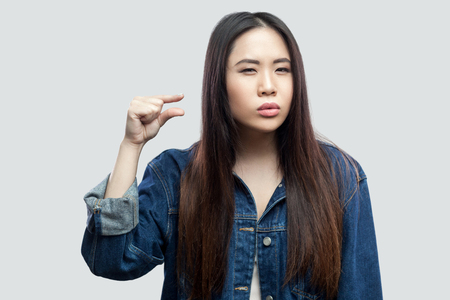 Give me few more. Portrait of beautiful brunette asian young woman in casual blue denim jacket with makeup standing and showing a little size with hand. studio shot, isolated on light grey background.