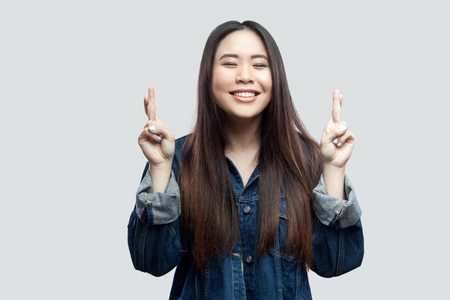 Portrait of hopeful beautiful brunette asian young woman in casual blue denim jacket with makeup standing with crossed finger and praying to win. indoor studio shot, isolated on light grey background.