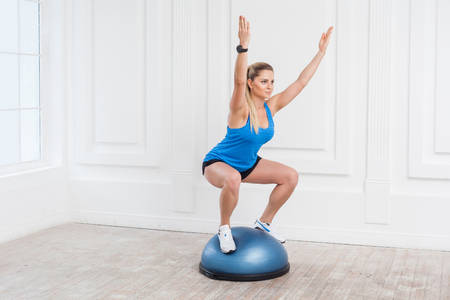 Concentration sporty beautiful young athletic blonde woman in black shorts and blue top working in gym doing exersice in bosu balance trainer, squats on fitness ball, holding balance with raised arms