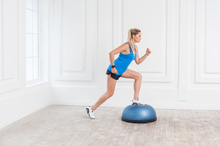Side view portrait of focused sporty young athletic blonde woman in black shorts and blue top working in gym doing exersice in bosu balance trainer, making one step on fitness ball. Indoor,studio shot