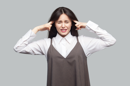 Portrait of sad confused beautiful young woman in white shirt and brown apron with makeup and brunette hair standing with headache and clenching teeth. indoor studio shot, isolated on grey background.