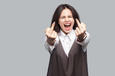 Portrait of angry young brunette hair woman in white shirt and brown apron standing with middle finger fuck sign gesture. looking at camera screaming. indoor studio shot, isolated on grey background.