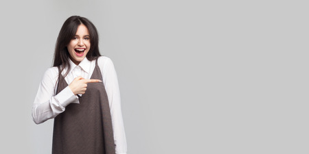 Portrait of excited beautiful young woman in white shirt and brown apron, makeup, brunette hair standing, pointing at copyspace, looking at camera with surprised face. studio shot on grey background.