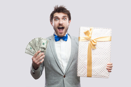 Handsome suprised young bearded man in gray suit and blue bow tie standing and holding gift box with yellow bow and many cash dollars with shocked face. Indoor, isolated, studio shot, grey background Stockfoto