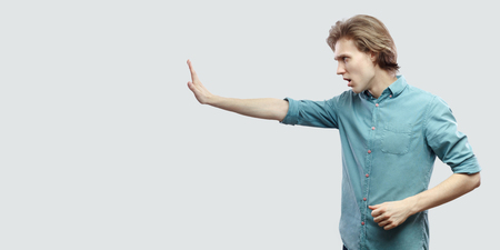Profile side view portrait of serious handsome long haired blonde young man in blue casual shirt standing with stop hand gesture sign. indoor studio shot, isolated on light grey background.