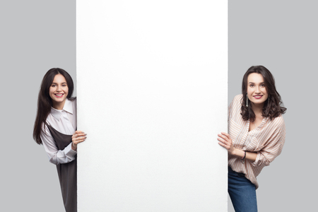 Portrait of two satisfied beautiful brunette young women in casual style standing near empty white blank copyspace and looking at camera with toothy smile. studio shot, isolated on grey background.