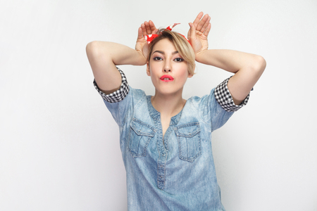 Portrait of funny beautiful young woman in casual blue denim shirt with makeup and red headband standing and looking at camera with bunny ears gesture hands. studio shot, isolated on white background. Stok Fotoğraf