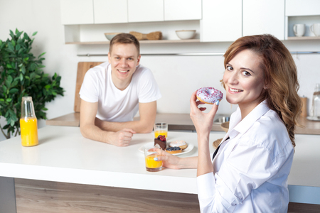 Young happy husband in the kitchen care for his wife. Woman eating donut and drinking juice. Lovestory, couple in love, happy people, future parents looking at camera and toothy smile
