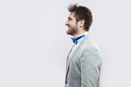 Profile side view portrait of happy satisfied handsome bearded man in casual grey suit and blue bow tie standing and looking straight with toothy smile. studio shot, isolated on light grey background. 免版税图像
