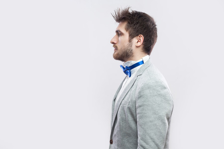 Profile side view portrait of serious handsome bearded man in casual grey suit, blue bow tie standing and looking straight wih calm serious face. indoor studio shot, isolated on light grey background.