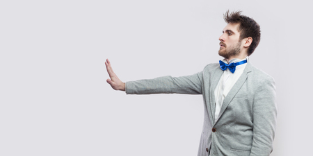 Profile side view portrait of serious handsome bearded man in casual grey suit, blue bow tie standing and looking straight with stop hand gesture sign. studio shot, isolated on light grey background. Stock Photo