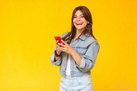 Portrait of beautiful happy brunette young woman with makeup in denim casual style standing, holding her red smart mobile phone, looking with toothy smile. studio shot, isolated on yellow background.