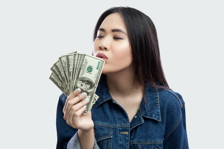 Loving money! Portrait of satisfied attractive young businesswoman in blue denim jacket standing, kissing with closed eyes and demonstrating fan of money. Indoor,studio shot, isolated, gray background Standard-Bild