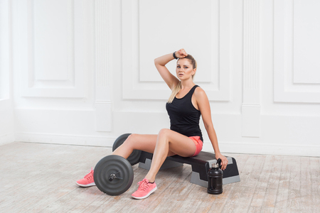 Portrait of sporty beautiful young athletic blonde woman in pink shorts and black top are sweated and have a rest after hard working on the gym. Indoor, studio shot, sport concept, looking at camera