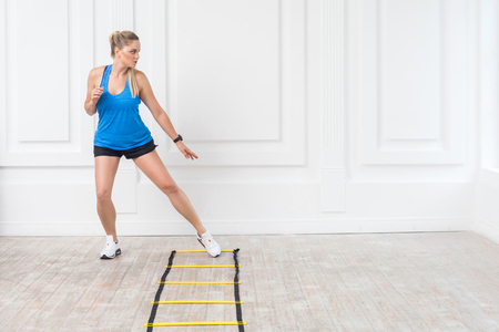 Full length of sporty beautiful young athletic blonde woman in black shorts and blue top are cardio workout with speed straps on floor and training on agility ladder drills in gym. Indoor, studio shot 写真素材