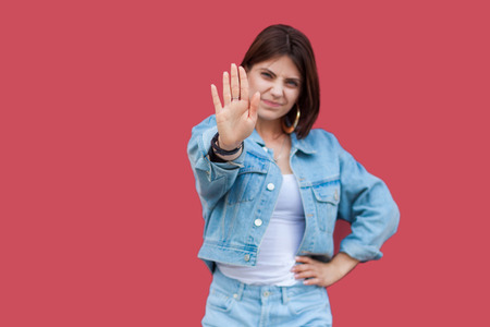 Portrait of warning beautiful brunette young woman with makeup in denim casual style standing with hand on waist and looking at camera with stop sign hands. studio shot, isolated on red background.