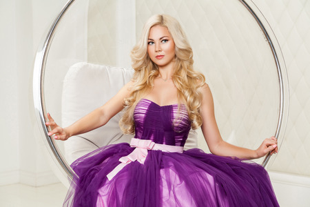 Portrait of attractive blonde elegance woman in fashionable purple dress with makeup and long wavy hairstyle sitting in hanged bubble chair at light room and looking away. indoor studio shot.
