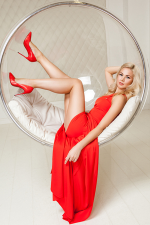 Sensual gorgeous fashionable blonde young woman in bright evening red dress with makeup and curly hairstyle lying and posing in hanged bubble chair, looking at camera with smile. indoor studio shot.
