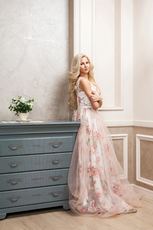 Beautiful blonde woman in pastel floral long puffy dress with makeup and long curly hairstyle leaning and posing near dresser at house and looking at camera. indoor studio shot. 免版税图像