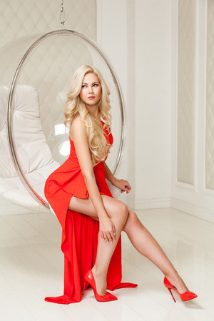 Sensual gorgeous blonde woman in bright evening red dress with makeup and long curly hairstyle sitting and posing in hanged bubble chair and looking away. indoor studio shot.