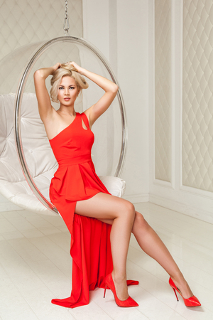 Sensual fashionable blonde young woman in bright evening red dress with makeup and hairstyle sitting and posing in hanged bubble chair and looking at camera and holding hair. indoor studio shot. Archivio Fotografico