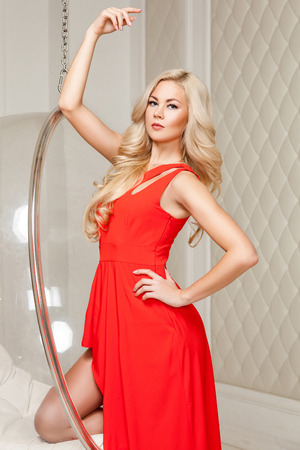 Sensual gorgeous blonde woman in bright red dress with makeup and long curly hairstyle standing posing and looking at camera while leaning on hanged bubble chair. indoor studio shot.