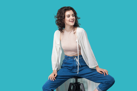 Portrait of happy successful satisfied beautiful young brunette woman in casual style sitting on chair, toothy smiling and looking away. indoor studio shot, isolated on blue background.