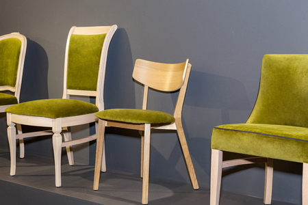 wooden chairs with green upholstered near grey wall . Foto de archivo