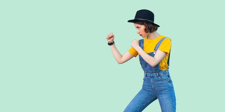 Profile side view portrait of serious young girl in blue denim overalls, yellow shirt, black hat standing with boxing fists and ready to attack. indoor studio shot isolated on light green background Archivio Fotografico