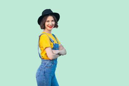 Happy pretty young hipster girl in blue denim overalls, yellow shirt and black hat standing, crossed arms and looking at camera with toothy smile. indoor studio shot isolated on light green background Archivio Fotografico