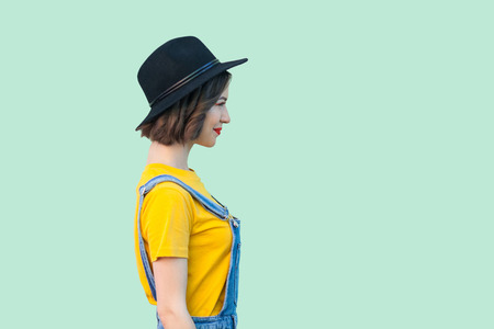 Profile side view portrait of pretty young hipster girl in blue denim overalls, yellow shirt and black hat standing, smiling and looking straight. indoor studio shot isolated on light green background Stock fotó