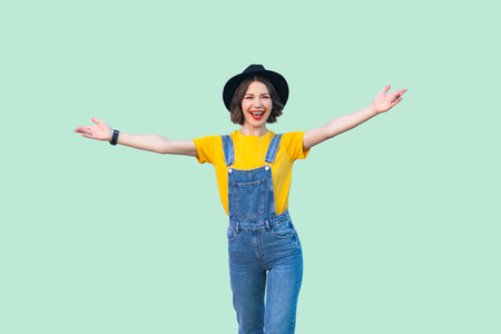 Portrait of happy pretty young girl in blue denim overalls, yellow shirt, black hat standing with raised arms and looking at camera with toothy smile. studio shot isolated on light green background.