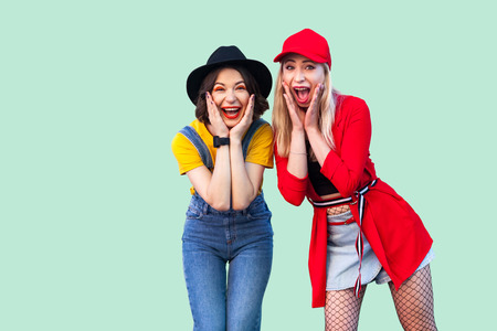Portrait of two best friend beautiful amazing happy fashionable hipster girls standing and screaming with unbelievable face, looking at camera. Indoor studio shot, isolated on green background.