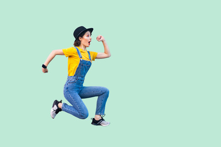 Profile side view portrait of surprised funny young hipster girl in blue denim overalls, yellow shirt and black hat jumping in super mario style. indoor studio shot isolated on light green background.