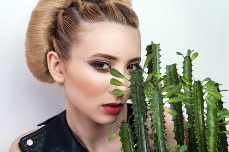 attractive woman with collected bun hairstyle posing with cactus in flowerpot isolated on white background, closeup. indoor, studio shot on grey background and looking at camera.