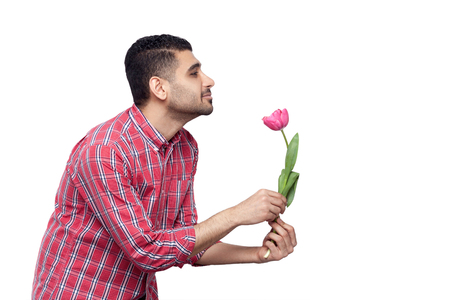 Side view profile portrait of handsome bearded young man in red checkered shirt standing and holding one tulip flower and smiling and looking straight. indoor studio shot, isolated on white background