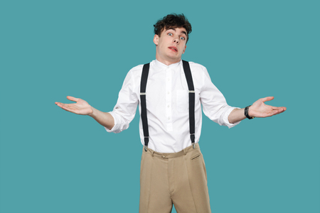 I don't know. confused man raised arms and looking at camera. Portrait of handsome hipster curly young businessman in classic casual white shirt and suspender. studio shot isolated on blue background. Foto de archivo