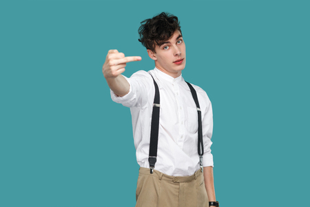 Man showing middle finger fuck sign and looking at camera. Portrait of handsome hipster curly young businessman in classic casual white shirt and suspender. studio shot isolated on blue background.