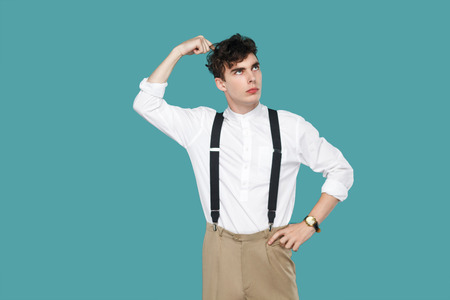 Confused man looking away and thinking. Portrait of handsome hipster curly young businessman in classic casual white shirt and suspender standing. indoor studio shot isolated on blue background.